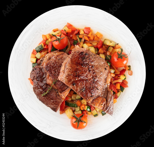 Ribeye steak with stir fried vegetables isolated on black