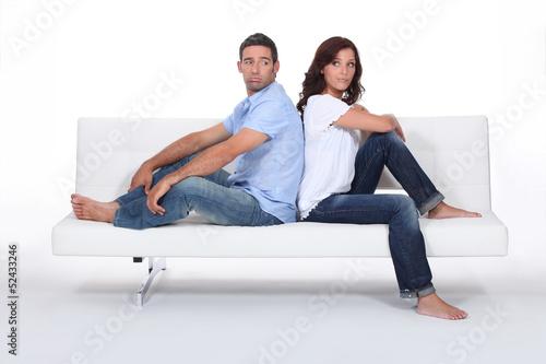 Couple back to back on white sofa