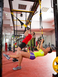 Fototapeta Fitness TRX training exercises at gym woman and man