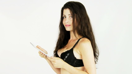 Woman in bikini reading tablet blowing kiss