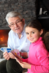 Old man playing card game with his granddaughter