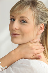 Blonde woman with hand on neck