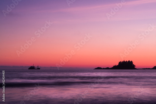 Ship across the ocean at Sunset, in Tofino beach, Canada