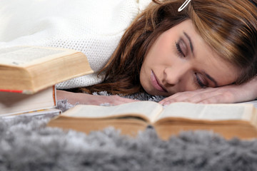 Female teenager asleep on a book