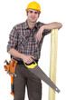 Builder with wood and handsaw