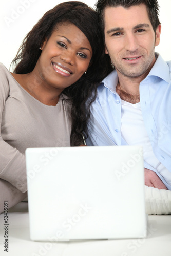 Mixed couple sat with laptop