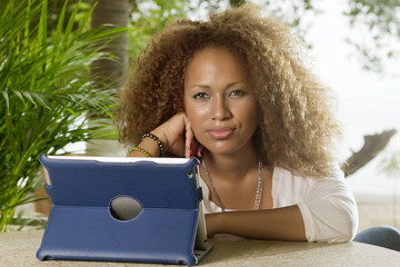Bella mujer sentada en un jardín frente a computadora