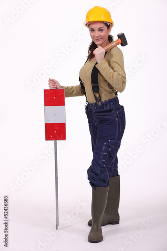 Woman with hammer over hershoulder signaling