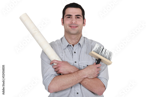 craftsman painter holding a wallpaper and a brush