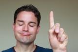 Mann mit erhobenem Zeigefinger schaut zufrieden