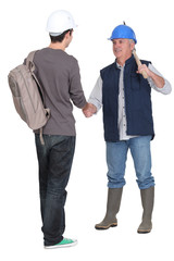 Manual worker giving new starter a warm welcome