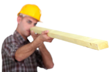Carpenter looking down at wooden plank