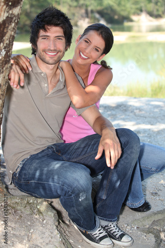 Couple sitting by a pond