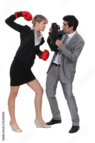 businesswoman threatening male colleague with boxing gloves