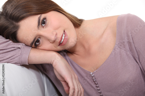 Brunette leaning on sofa