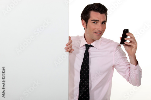 Salesman with a cellphone and blank board