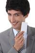 Confident businessman holding calling card