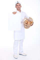 A baker presenting a blank poster.