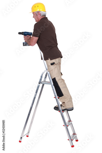 Tradesman standing on a stepladder and using a power tool