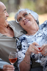 Elderly drinking wine.