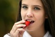 Brunette eating a delicious strawberry