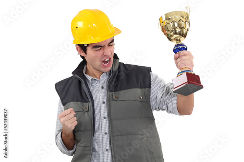Male builder holding trophy