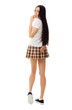 Modest school girl in plaid skirt and sneakers