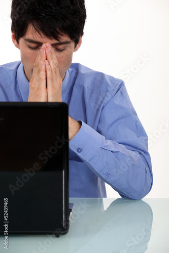 young businesswoman seated in front of laptop looking exhausted