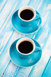 Vertical shot of two espresso cups with black coffee