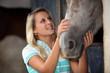 Teen stroking horse