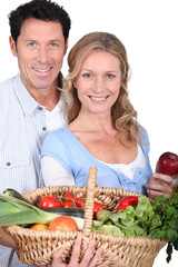 Couple with vegetable basket.