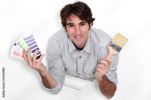 Man holding colour samples and a paintbrush