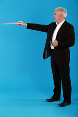 A businessman pointing with a ruler.