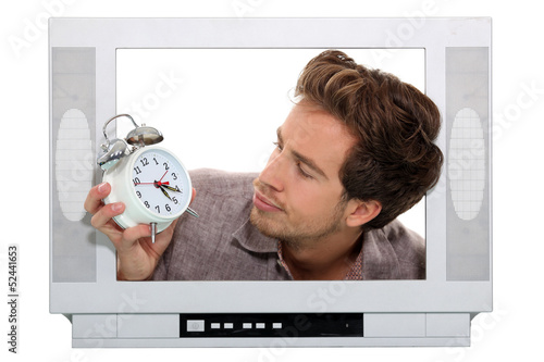 Man inside television looking at alarm clock