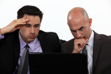 Stressed businessmen looking at laptop screen
