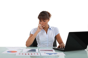 Woman sat at desk surrounded by graphs