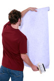 Man with a roll of wallpaper
