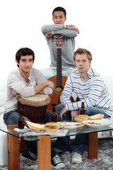 Young men at home with musical instruments
