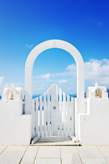 Beautiful white wooden door above aegean sea in Oia