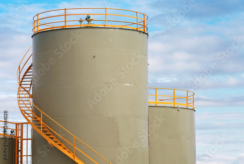Gray cylindrical fuel tanks with yellow railings