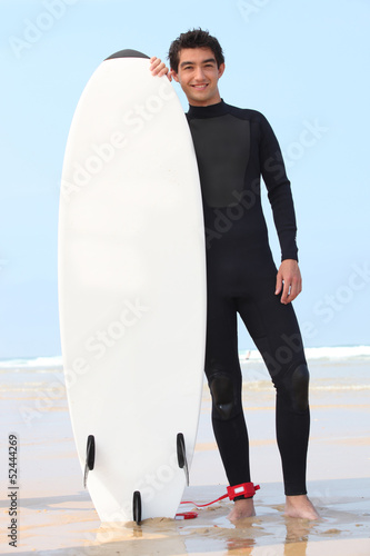 young surfer posing with board