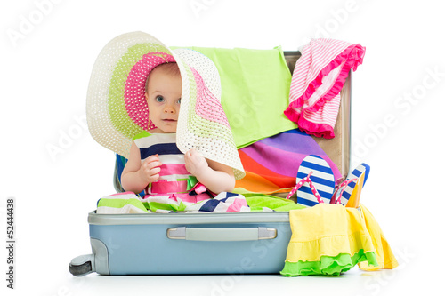 Baby girl sitting in suitcase with  things for vacation travel
