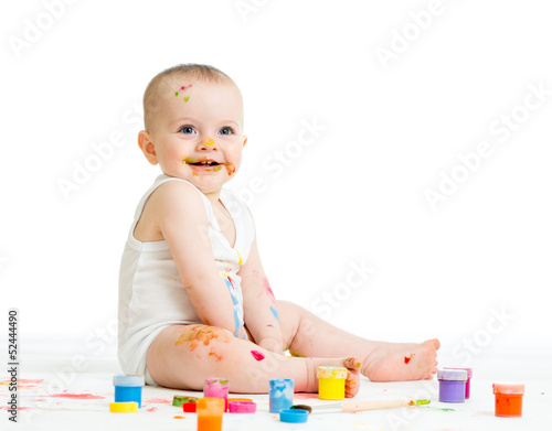 smiling baby drawing with a finger's paints