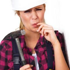 Junge Heimwerkerin mit Hammer hat Schmerzen am Finger