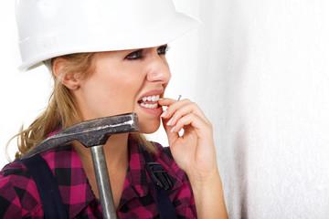Junge Heimwerkerin mit Hammer traut sich nicht
