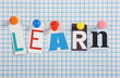 The word Learn in cut out magazine letters on graph paper