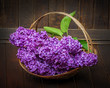 pink lilac in a basket and old wooden background