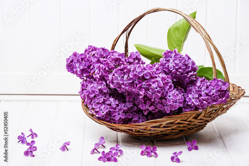 Keuken foto achterwand Lilac pink lilac in a basket on a white wooden background