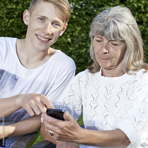 Young man teaching senior female to use a smartphone