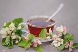 Cup of tea with blooming apple tree branch